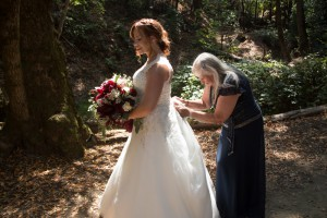 Mother of the bride helping her daughter with her gown